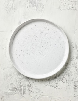 Empty white plate on kitchen table, top view