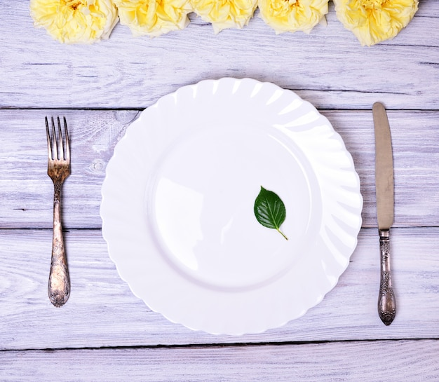 Empty white plate and metal fork and knife