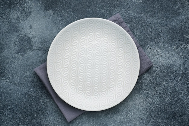 Empty white plate on a napkin dark stone table. copy space.