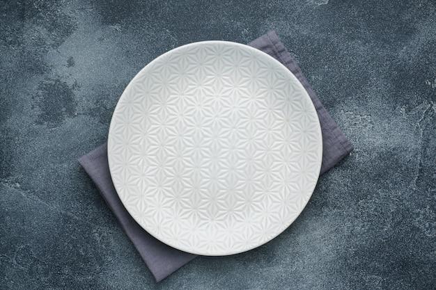 냅킨 어두운 돌 테이블에 빈 흰색 접시. 공간을 복사하십시오.