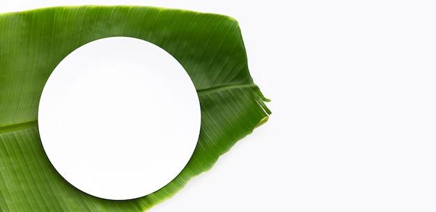Пустая белая тарелка на банановом листе