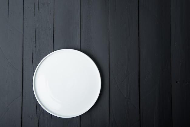 검은 나무 배경에 빈 흰색 접시