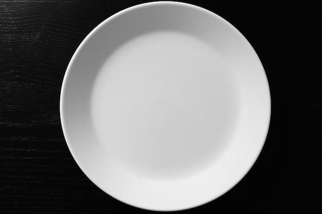 黒い木製のテーブルの空の白いプレート