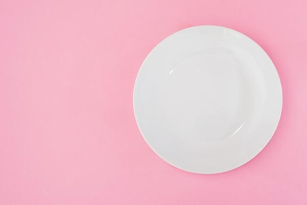 コピースペースとピンクの背景に空の白いプレート。