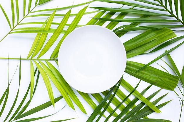 Пустая белая тарелка на тропических пальмовых листьях на белом фоне. вид сверху