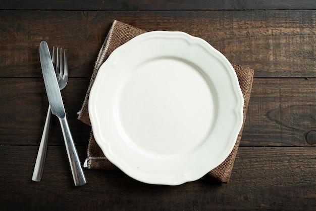 나무 테이블에 빈 흰색 접시입니다.