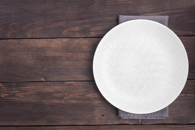 나무 소박한 배경에 빈 흰색 접시입니다. 복사 공간이 있는 상위 뷰입니다.