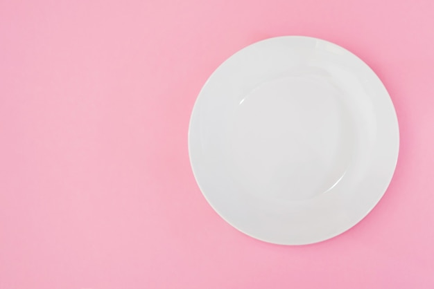 Empty white plate on pink background with copy space.