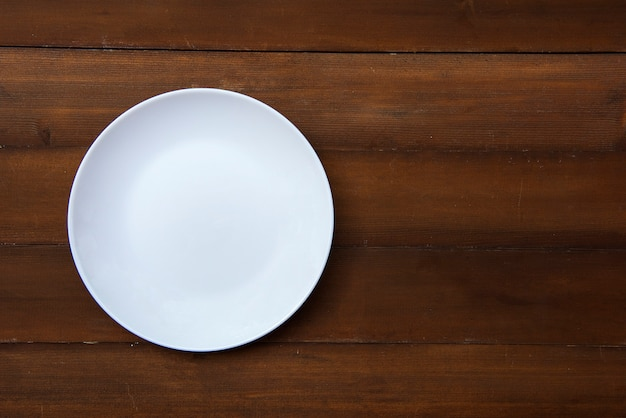 An empty white plate placed on a wooden floor