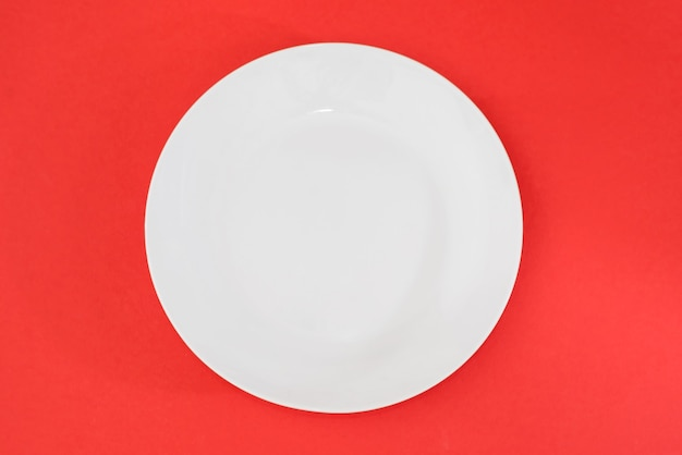 Empty white plate on a red background. view from above.