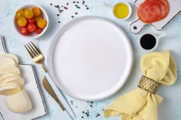 Empty white plate surrounded by cutlery and fresh vegetables top view on blue background