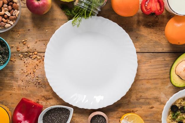 마른 과일로 둘러싸인 빈 흰색 접시; 야채; 나무 테이블에 과일