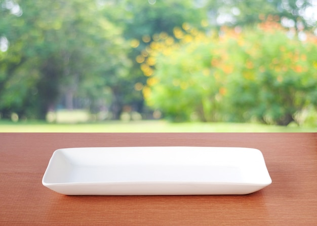 Empty white plate on table over blur park nature outdoor in spring and summer with bokeh background