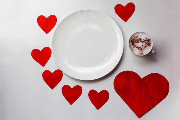 Empty white plate on the table with red hearts around and cup with a hot drink and a painted heart on foam.