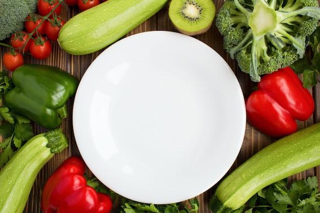 空の白いプレート、茶色の背景に野菜と果物。健康食品の食材。平面図。コピースペース。