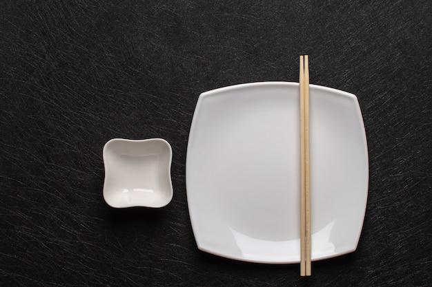Пустая белая тарелка с палочками для еды и соусник на темном столе. японский стиль еды. вид сверху