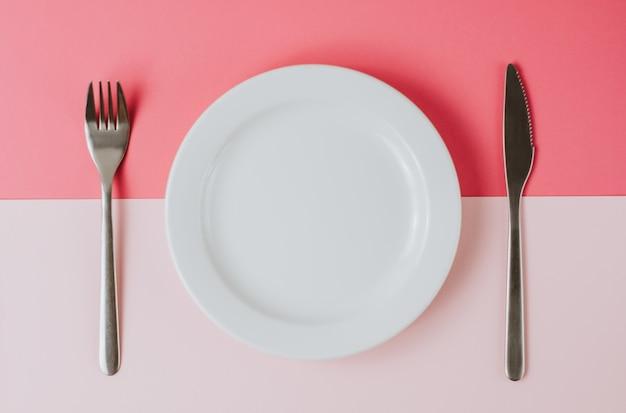 Пустая белая тарелка со столовыми приборами на розовом фоне.