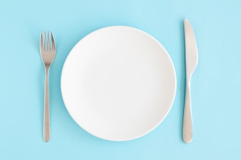 Empty white plate with fork and butter knife over blue background