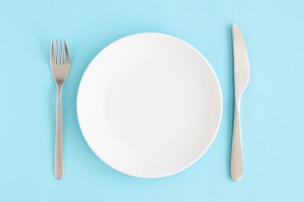 파란색 배경 위에 포크와 버터 나이프와 빈 흰색 접시