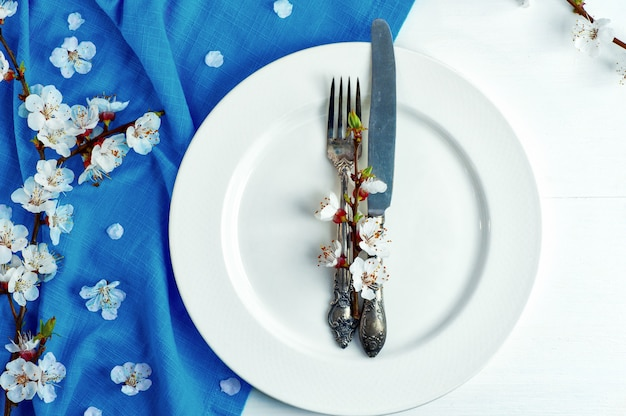 Empty white plate with a fork and knife