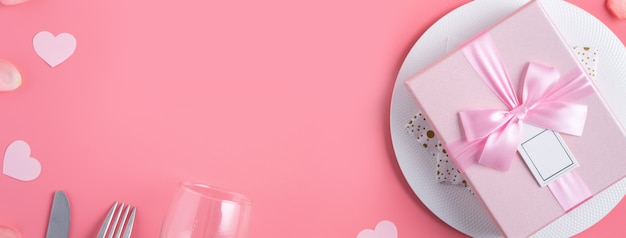 Пустая белая тарелка с подарком и лепестками роз для специальной праздничной еды свидания дня святого валентина.