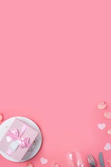 Пустая белая тарелка с подарком и лепестками роз для специальной праздничной еды свидания дня святого валентина. Premium Фотографии