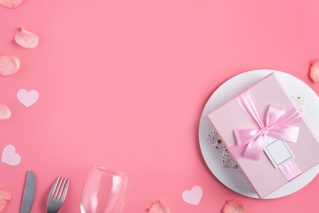 Empty white plate with gift and rose petals for valentine's day special holiday dating meal concept.