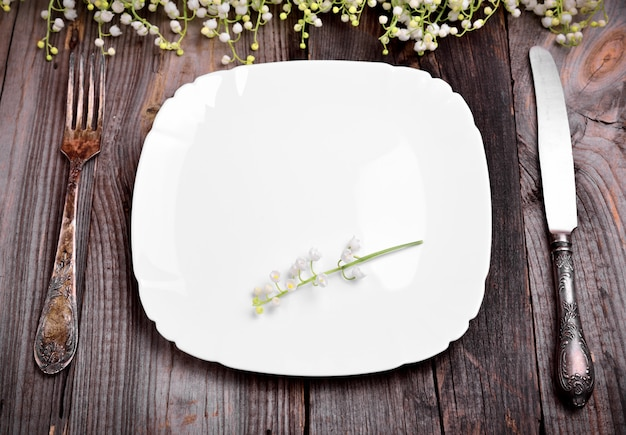 Empty white plate with iron cutlery