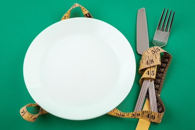 Piatto bianco vuoto con nastro di misurazione, concetto di perdita di peso