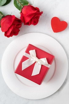 Empty white plate with tableware for valentine's day special holiday dating meal concept.