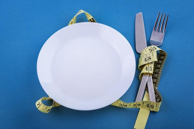 Piatto bianco vuoto con nastro adesivo di misurazione giallo legato. concetto di perdita di peso. primo piano delle posate.