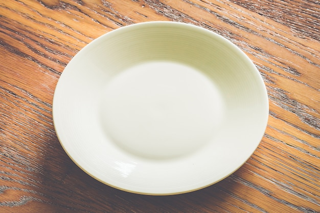 Empty white plate on wood background