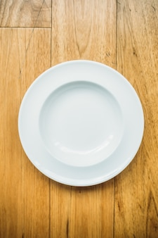 Empty white plate on wooden background
