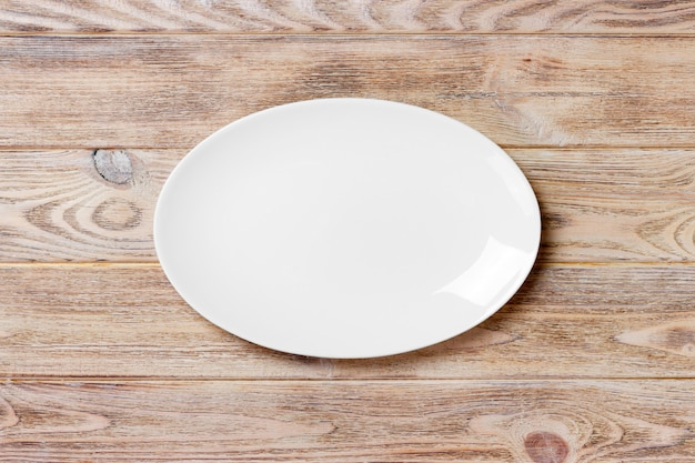 Empty white plate on wooden table. top view