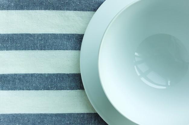 Пустые белые тарелки и чаша со скатертью