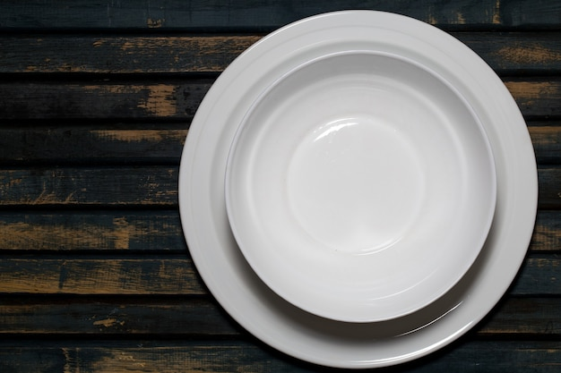 Empty white plates on a wooden table