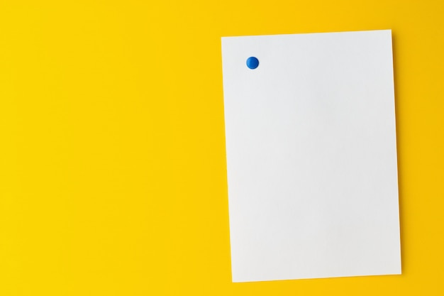 空の白いシートは黄色の背景に固定されています