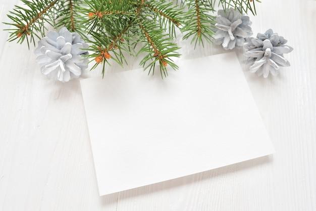 モミの枝の白いクリスマスの背景に空の白い紙