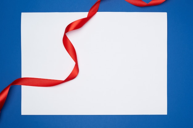 Empty white sheet of paper and red silk twisted ribbon
