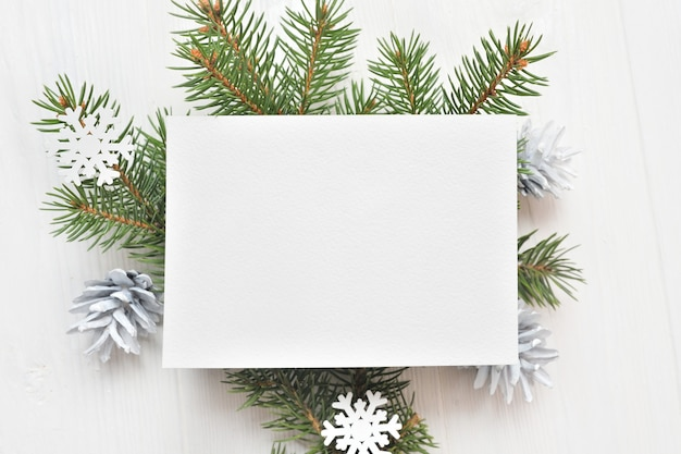 Empty white sheet of paper on a white christmas background of fir branches and cones.