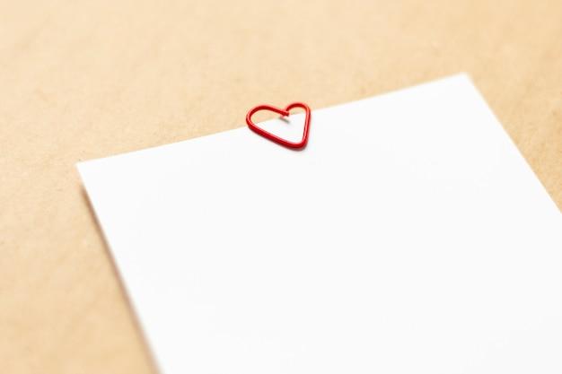 크래프트 종이 배경에 빈 흰색 시트입니다. 하트 모양의 빨간 종이 클립. 확대
