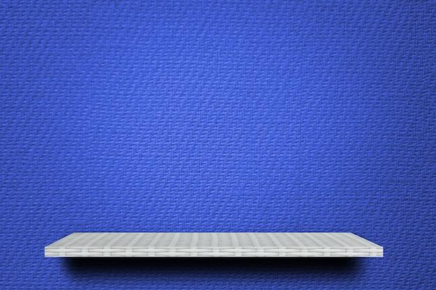 Empty white shelf on blue fabric background