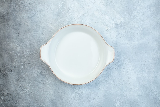 Empty white soup plate on gray surface with distressed surface with free space