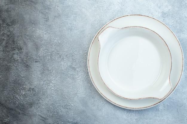 여유 공간이있는 고민 된 표면이있는 반 어두운 밝은 회색 표면의 왼쪽에 빈 흰색 수프 접시