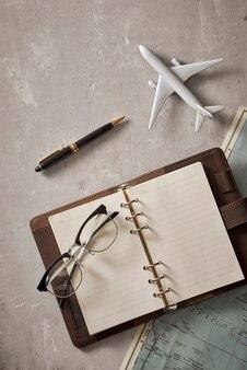 テキストや広告を配置できるノートブックの空白を空にします。飛行機、虫眼鏡、地図上の眼鏡。ロマンチックな旅行