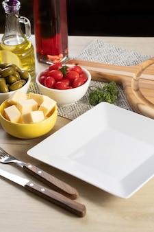 Пустая белая квадратная тарелка на столе с сыром, оливками и помидорами черри.