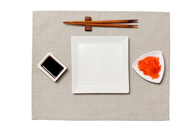 회색 냅킨 표면에 초밥, 생강, 간장 젓가락으로 빈 흰색 사각형 접시