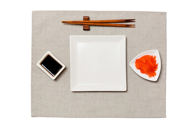 Empty white square plate with chopsticks for sushi, ginger and soy sauce on grey napkin surface
