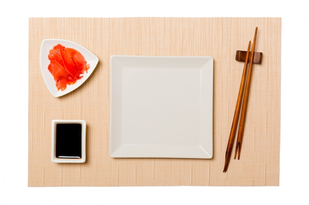 Empty white square plate with chopsticks for sushi and soy sauce, ginger on brown sushi mat background.
