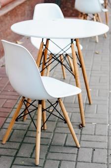 カフェの近くの通りにある空の白いテーブルと椅子。都会的な装飾。